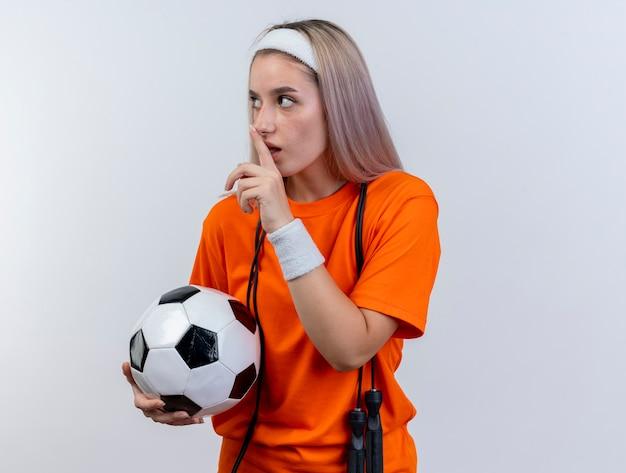 Angstig jong kaukasisch sportief meisje met beugels en met touwtjespringen om de nek hoofdband en polsbandjes dragen houdt bal en gebaren stilte teken kijken kant op witte muur
