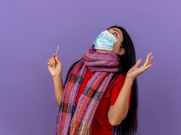 Angstig jong kaukasisch ziek meisje dat masker en sjaal draagt die thermometer houdt die hand in lucht houdt die tot god bidt geïsoleerd op paarse muur met exemplaarruimte