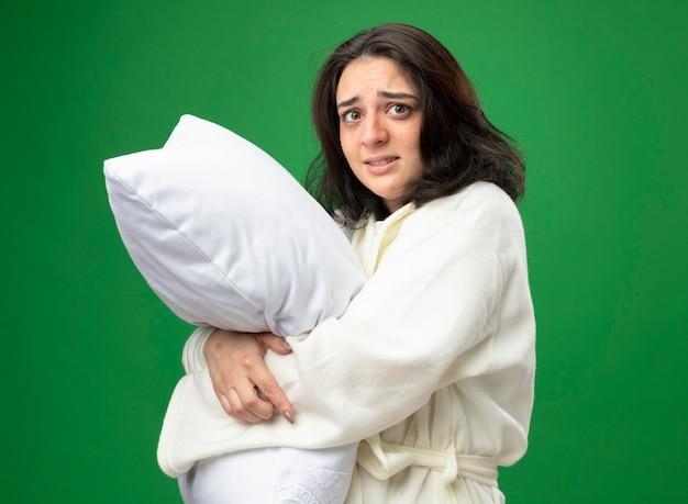 Angstig jong kaukasisch ziek meisje die gewaad dragen die zich in profielmening bevinden die hoofdkussen koesteren die camera bekijken die op groene achtergrond wordt geïsoleerd