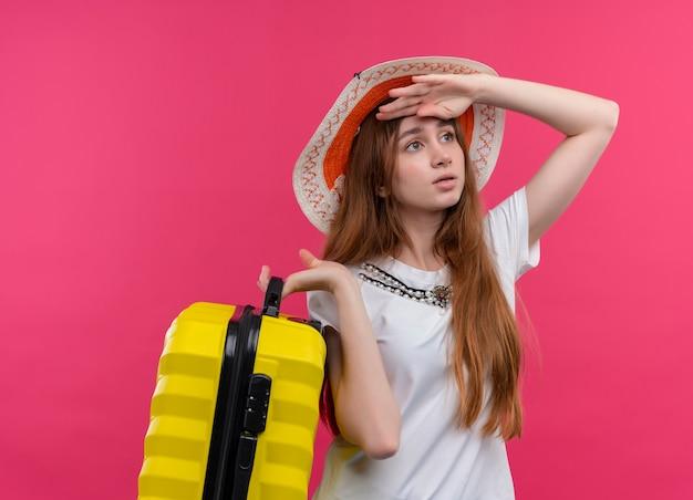 Angstig jong reizigersmeisje die de koffer van de hoedenholding dragen die hand op voorhoofd zet die afstand op geïsoleerde roze ruimte bekijkt