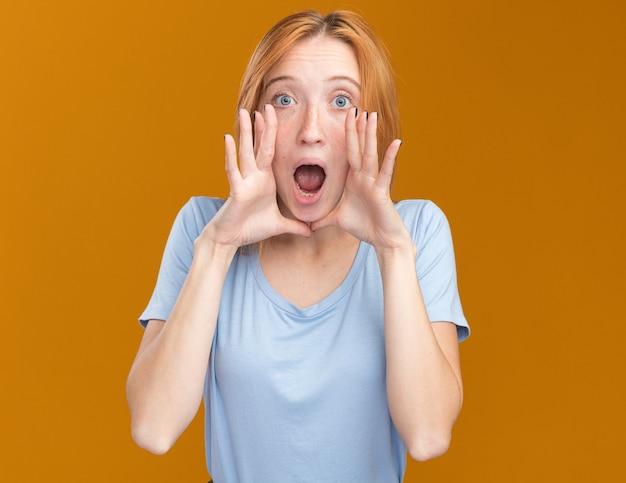 Angstig jong roodharig gembermeisje met sproeten die handen dicht bij mond op sinaasappel houden