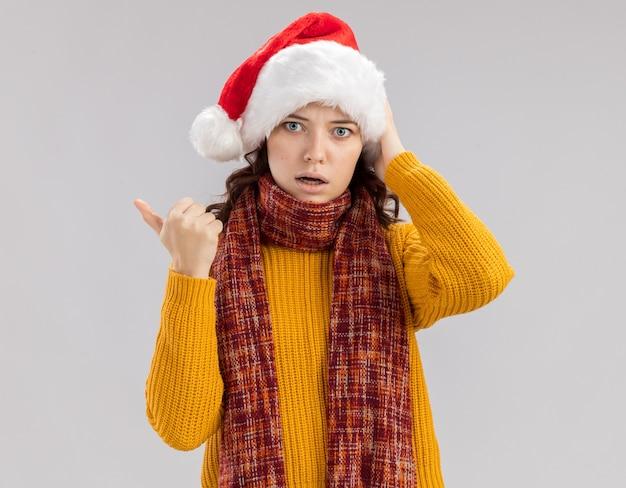 Angstig jong slavisch meisje met kerstmuts en met sjaal om de nek wijzend naar de zijkant geïsoleerd op een witte muur met kopieerruimte
