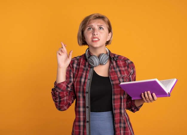 Angstig jong slavisch studentenmeisje met hoofdtelefoon die rugzak draagt, kruist vingers en houdt boek vast