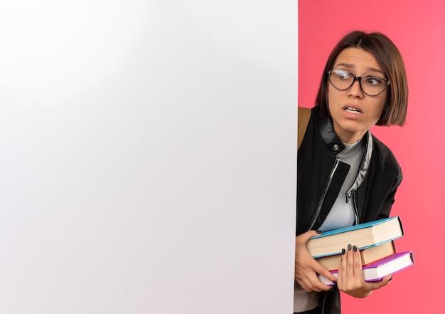Angstig jong studentenmeisje die glazen en achterzak dragen die boeken bekijken die kant van achter witte muur bekijken die op roze met exemplaarruimte wordt geïsoleerd