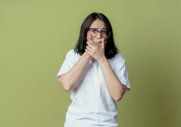 Angstig jong vrij kaukasisch meisje dat glazen draagt ?? die handen op mond zetten die op olijfgroene achtergrond met exemplaarruimte wordt geïsoleerd