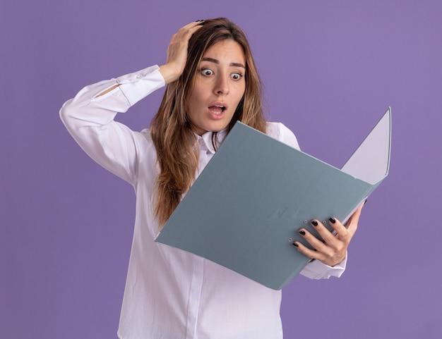 Angstig jong vrij kaukasisch meisje legt hand op hoofd vast te houden en dossiermap op paars te bekijken