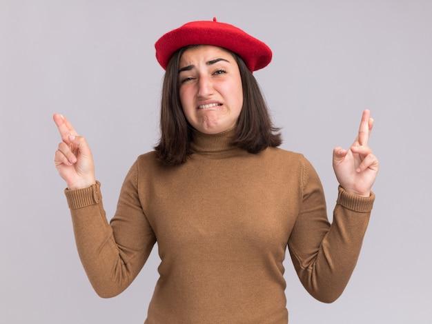 Angstig jong, vrij kaukasisch meisje met barethoed staat met gekruiste vingers