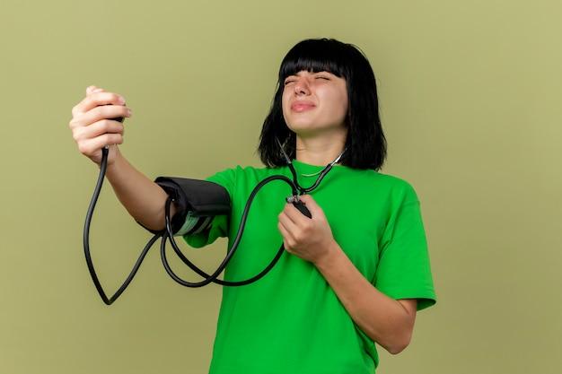 Angstig jong ziek kaukasisch meisje dat een stethoscoop draagt die haar druk met bloeddrukmeter meet met gesloten ogen geïsoleerd op olijfgroene muur met exemplaarruimte