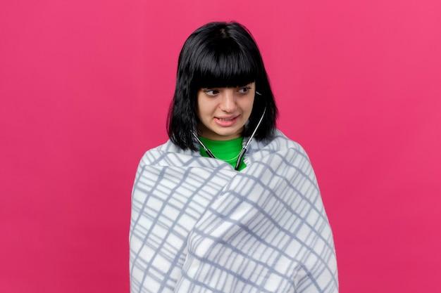 Angstig jong ziek kaukasisch meisje dat in plaid wordt verpakt die stethoscoop draagt die kant bekijkt die op karmozijnrode muur met exemplaarruimte wordt geïsoleerd
