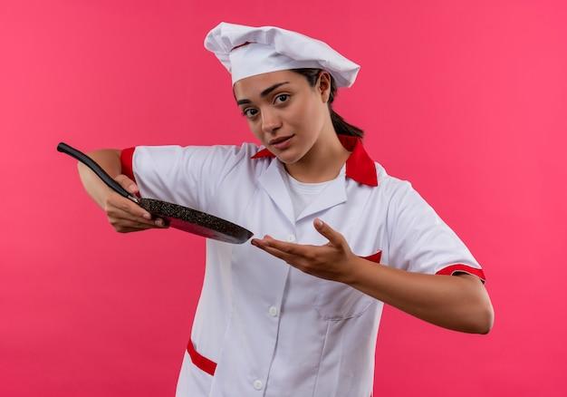 Angstig kaukasisch kokmeisje in uniform chef-kok houdt koekenpan en punten met hand geïsoleerd op roze achtergrond met kopie ruimte