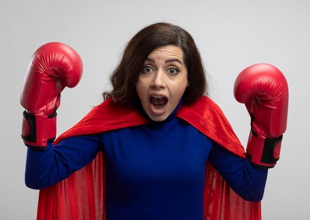Angstig kaukasisch superheldmeisje met rode cape die het dragen van bokshandschoenen staat
