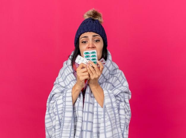 Angstig kaukasisch ziek meisje dragen winter hoed en sjaal verpakt in plaid bedrijf verpakkingen van medische pillen kijken naar hen geïsoleerd op karmozijnrode achtergrond met kopie ruimte