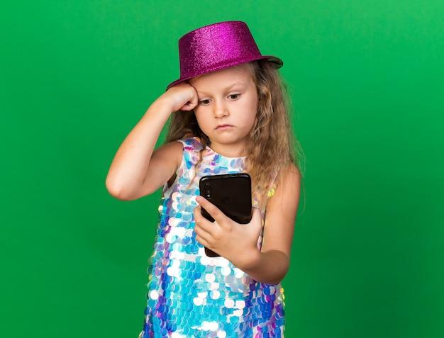 Angstig klein blond meisje met paarse feestmuts houden en kijken naar telefoon geïsoleerd op groene muur met kopie ruimte