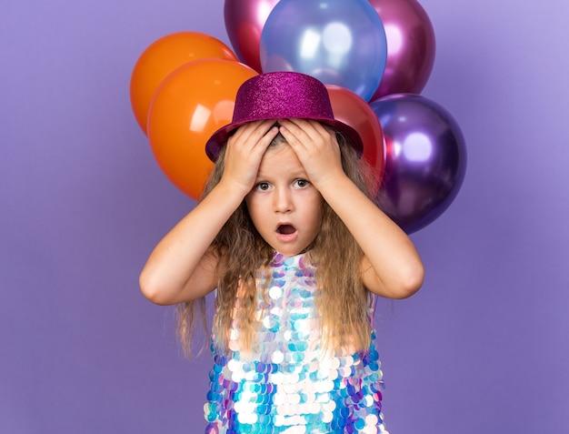 Angstig klein blond meisje met violet feestmuts handen op het voorhoofd staande met helium ballonnen geïsoleerd op paarse muur met kopie ruimte