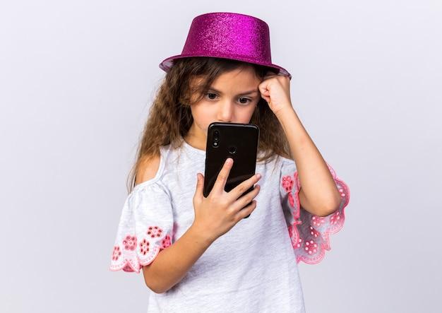 Angstig klein kaukasisch meisje met paarse feestmuts hand zetten voorhoofd houden en kijken naar telefoon geïsoleerd op een witte muur met kopie ruimte