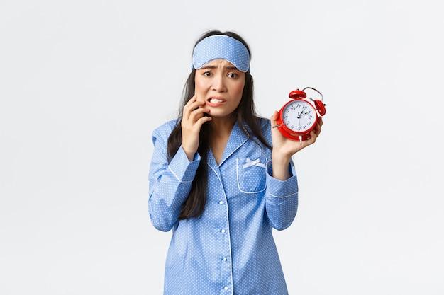 Angstig schattig aziatisch meisje dat alarm en paniek toont, bezorgde vinger bijt, er nerveus uitziet, niet weet wat te doen om te laat te zijn, zich 's ochtends verslapen om te werken, een pyjama en een slaapmasker draagt.