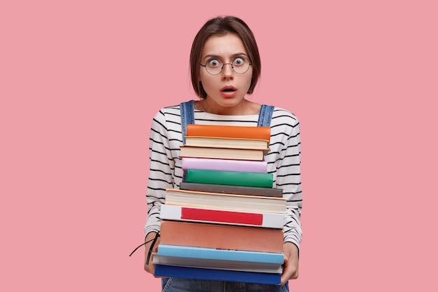 Angstig schoolmeisje draagt een stapel handboeken, draagt een optische bril en een gestreepte trui, kijkt verontwaardigd naar de camera