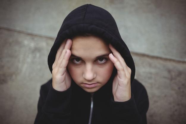 Angstig tienermeisje in zwart jasje met een kap camera kijken