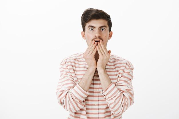 Angstig verward gewoon europees mannelijk model met snor, handpalmen rond geopende mond vasthoudend en starend met onnozele uitdrukking, nerveus en bezorgd
