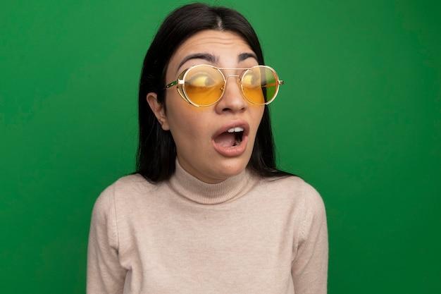 Angstig vrij donkerbruin kaukasisch meisje in zonnebril kijkt kant op groen