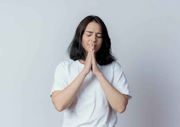 Angstig vrij kaukasisch meisje bidden met gesloten ogen geïsoleerd op een witte achtergrond met kopie ruimte