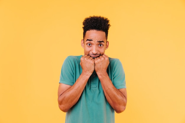 Angstige afrikaanse man poseren. bezorgd zwarte man in heldergroene t-shirt reputatie.