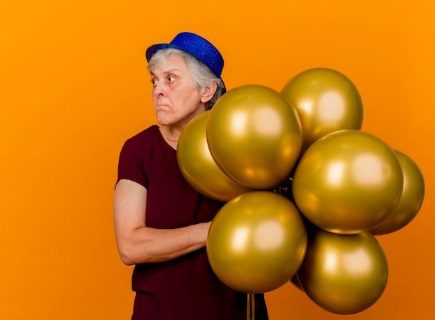 Angstige bejaarde vrouw met feestmuts houdt helium ballonnen kijken kant geïsoleerd op oranje muur