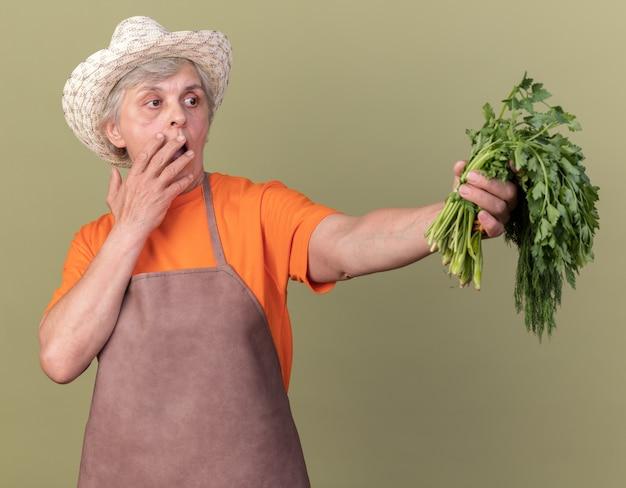 Angstige bejaarde vrouwelijke tuinman tuinieren hoed dragen legt hand op mond en houdt bos van koriander dille op olijfgroen