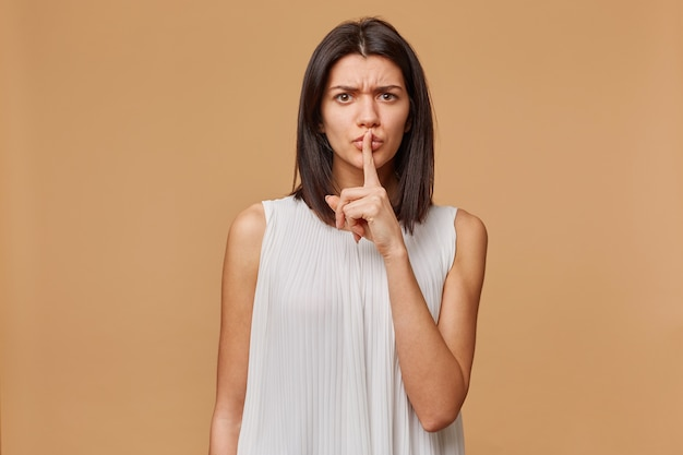 Angstige, bezorgde, bezorgde, nerveuze, paniekerige, agressieve, boze vrouw toont een gebaar van stilte, houdt een wijsvinger bij de mond en roept op tot privacy, geheim, over beige muur