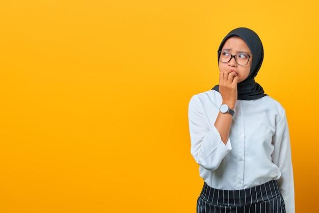 Angstige bezorgde jonge aziatische vrouw bang voor iets geïsoleerd over gele achtergrond