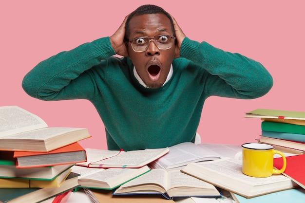 Angstige, donkere man staart stomverbaasd, houdt zijn handen op zijn hoofd, opent zijn mond wijd, schrikt voor komend examen, studeert literatuur