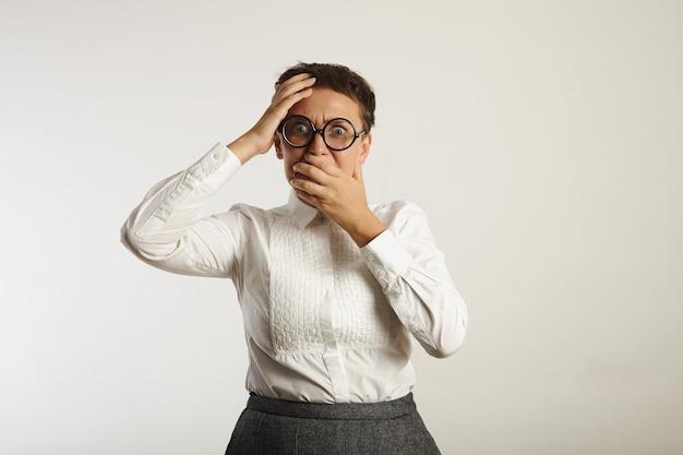 Angstige emotionele jonge vrouw bedekt haar mond in afgrijzen geïsoleerd op wit
