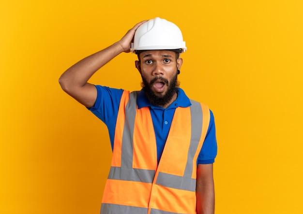 Angstige jonge afro-amerikaanse bouwer man in uniform met veiligheidshelm hand op zijn hoofd zetten geïsoleerd op oranje muur met kopieerruimte