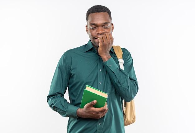 Angstige jonge afro-amerikaanse student met rugzak die boek vasthoudt en in zijn vingers bijt