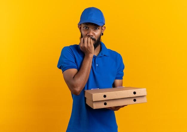 Angstige jonge bezorger die pizzadozen vasthoudt en op zijn nagels bijt geïsoleerd op een oranje muur met kopieerruimte