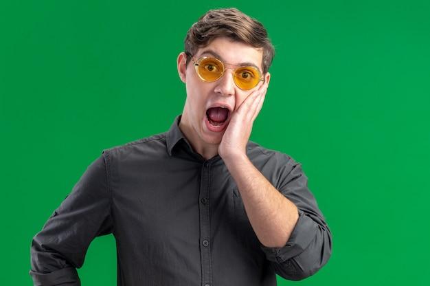 Angstige jonge blanke jongen met een zonnebril die zijn hand op zijn gezicht legt en naar de camera kijkt