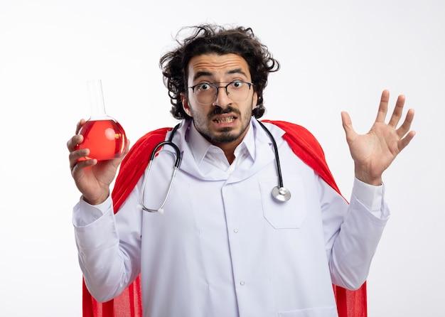Angstige jonge blanke man in optische bril dragen arts uniform met rode mantel en met een stethoscoop om de nek staat met opgeheven hand en houdt rode chemische vloeistof in glazen kolf