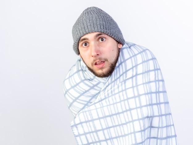 Angstige jonge blanke zieke man met een winterhoed gewikkeld in een bord