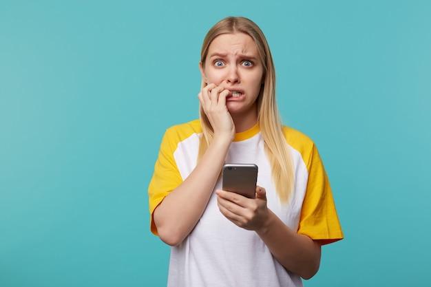 Angstige jonge blauwogige blonde vrouw met natuurlijke make-up fronst haar wenkbrauwen terwijl ze bang kijkt en hand op haar gezicht houdt, geïsoleerd op blauw