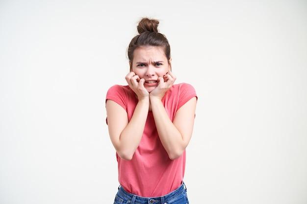 Angstige jonge blauwogige brunette vrouw met casual kapsel houdt haar gezicht met opgeheven handen terwijl ze bang naar de camera kijkt, geïsoleerd op witte achtergrond