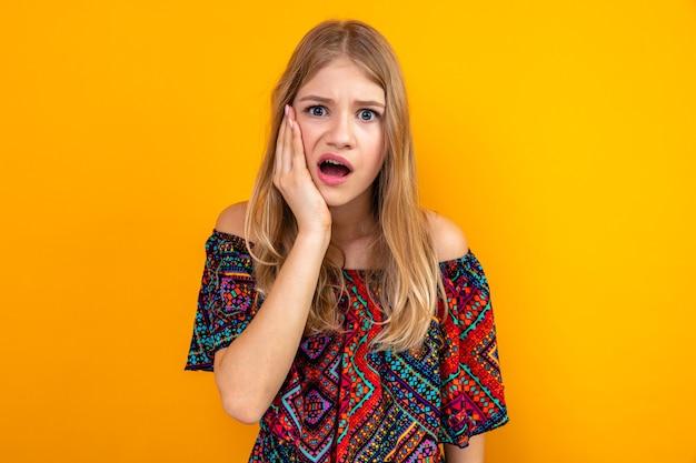Angstige jonge blonde slavische vrouw die haar hand op haar gezicht legt en kijkt