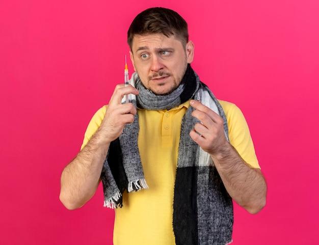 Angstige jonge blonde zieke slavische man met sjaal houdt ampul en kijkt naar spuit op roze