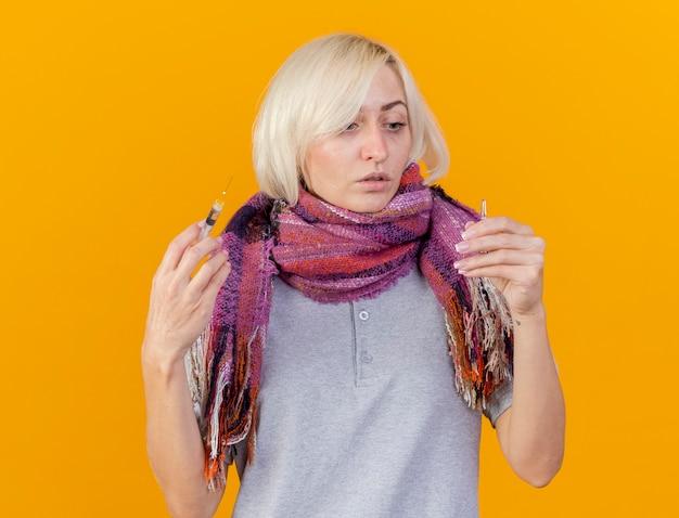 Angstige jonge blonde zieke slavische vrouw die sjaal draagt houdt spuit