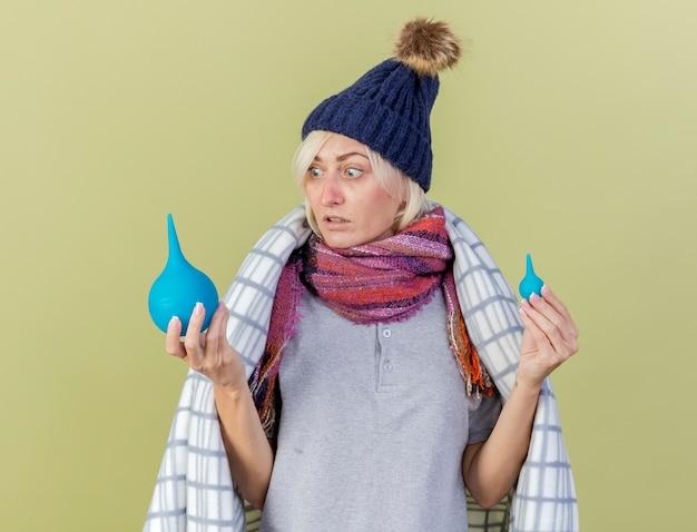 Angstige jonge blonde zieke slavische vrouw met muts en sjaal gewikkeld in geruite houdt en kijkt naar klysma's geïsoleerd op olijfgroene muur met kopie ruimte