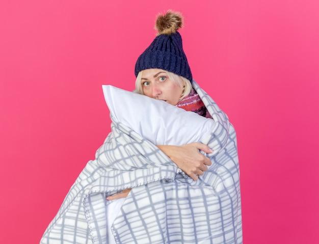 Angstige jonge blonde zieke vrouw die de wintermuts en sjaal draagt die in geruite knuffels kussen wordt verpakt die voorzijde bekijkt die op roze muur wordt geïsoleerd