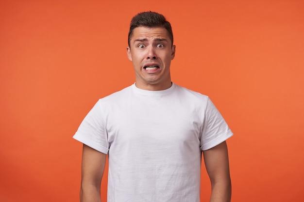 Angstige jonge bruinogige brunette man met kort kapsel verbaasd zijn ogen afronden terwijl hij bang naar de camera keek, staande over de oranje achtergrond