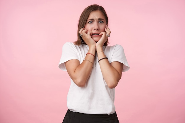 Angstige jonge bruinogige brunette vrouw met bob kapsel houdt haar gezicht vast met opgeheven handen terwijl ze bang naar voren kijkt, staande over roze muur