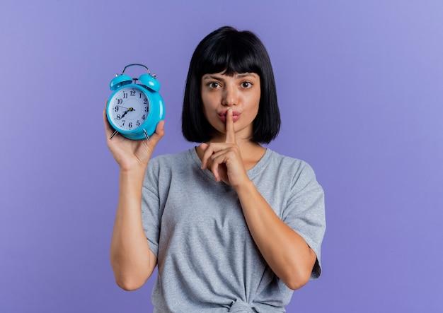 Angstige jonge brunette blanke vrouw houdt wekker en gebaren wees stil teken geïsoleerd op paarse achtergrond met kopie ruimte