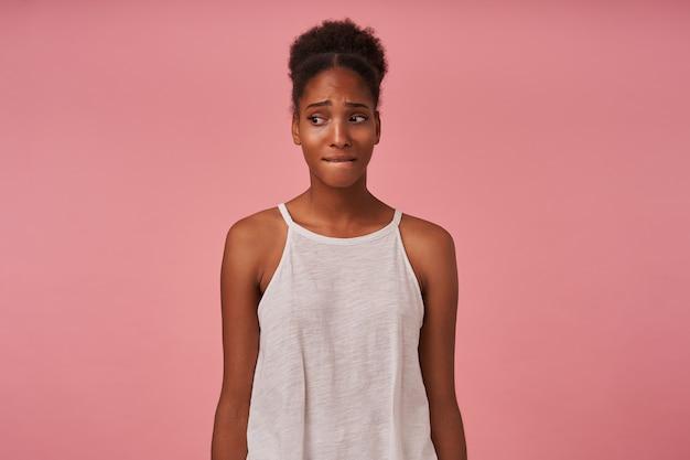 Angstige jonge gekrulde brunettened dame bijt op haar onderlip en fronsende wenkbrauwen terwijl ze droevig opzij kijkt, geïsoleerd over roze muur met handen naar beneden