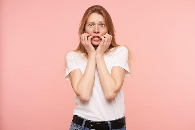 Angstige jonge groenogige roodharige vrouw met natuurlijke make-up die haar gezicht met opgeheven handen vasthoudt terwijl ze bang naar de camera kijkt, staande over roze achtergrond